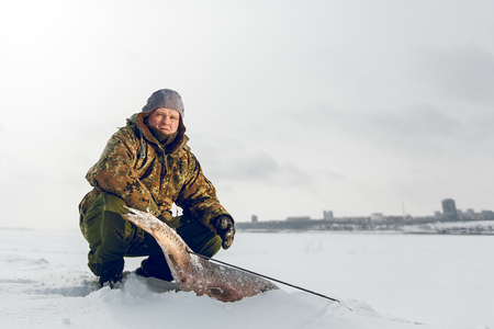 Spearfishing with speargun shot a big fish under the ice of the river Volga near Volgograd area Фото со стока