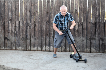 An elderly man tries to drive a scooter to teach his sons. Фото со стока