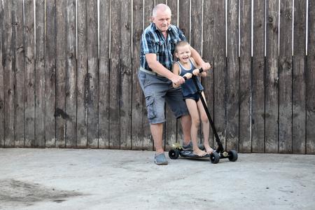 Отец и сын играет на дороге в дневное время. Люди с удовольствием на открытом воздухе. Концепция дружной семьи.