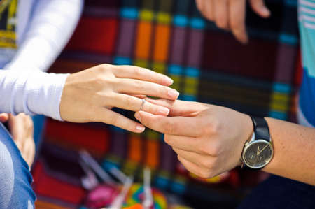 fingers put together: A man puts a woman an engagement ring at a picnic in the background, engagement
