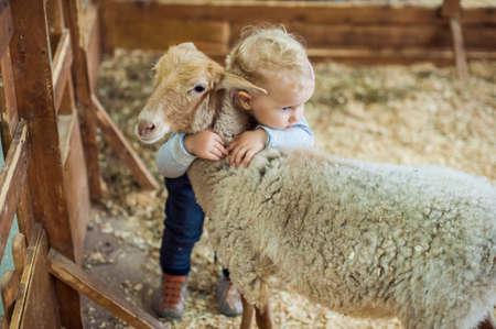 Niño de la muchacha que abraza el cordero en la granja