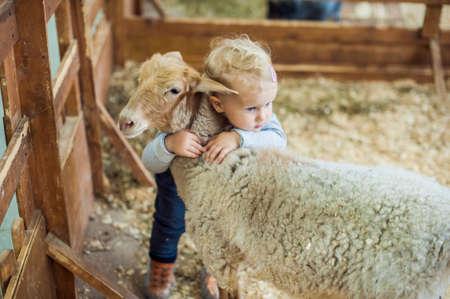 Niño de la muchacha que abraza el cordero en la granja Foto de archivo