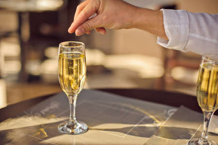 A man throws a wedding ring in a glass of champagne to ask his girlfriend to be his wife