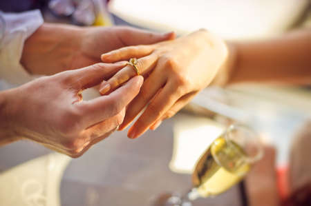 fingers put together: The man wears a wedding ring on womans hand.