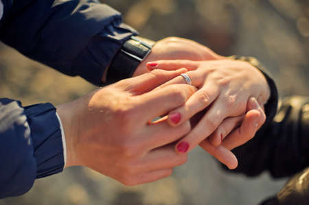 The man wears a wedding ring on womans hand Stock Photo