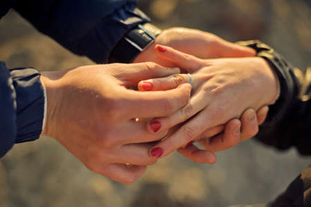 fingers put together: The man wears a wedding ring on womans hand Stock Photo