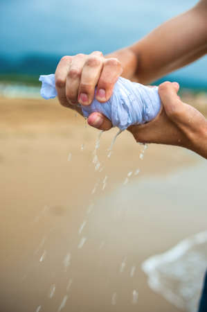 Hands wring out a wet T-shirt, sea Stock Photo