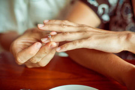 A man puts a woman an engagement ring in a cafe