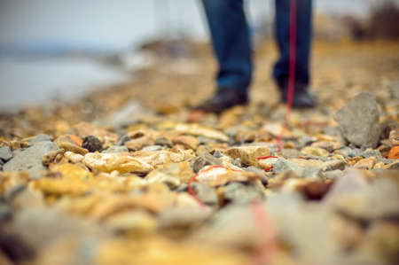 hilo rojo: hilo rojo se tira a través de la playa rocosa