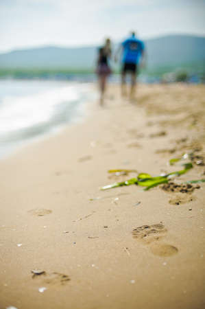 long toes: A man and a woman go on sand, footprints in the sand