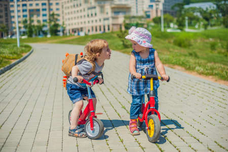Toddlers Boy and girl kissing on balance bikes in summer park, kids sport
