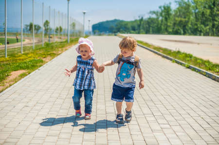 2 way: Toddlers Boy and girl go on a path past the football field in a summer park Stock Photo
