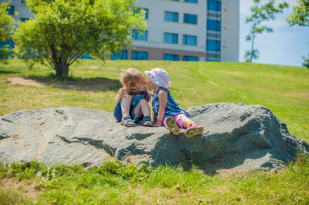 large rock: Toddlers Boy and girl kissing in summer park on a large rock