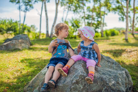 large rock: Toddlers Boy and girl sitting in summer park on a large rock