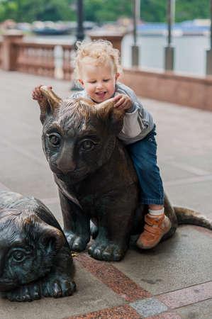Tiger cub: Una chica se sienta en la estatua de Tiger Cub Foto de archivo