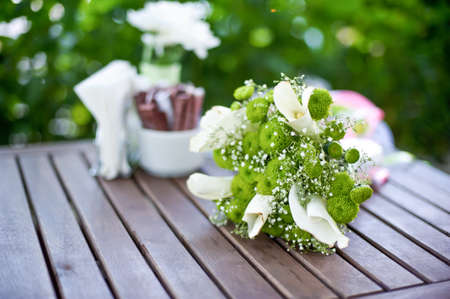 feminine background: green white bridal bouquet on a wooden table