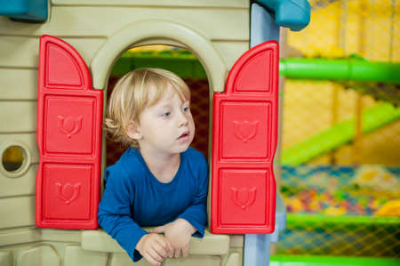 one room school house: Toddler boy looks out of the house to the game room