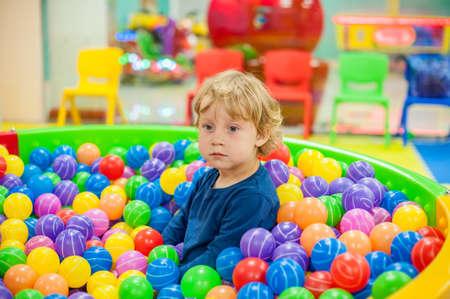 todler garçon assis dans les boules dans la salle de jeu