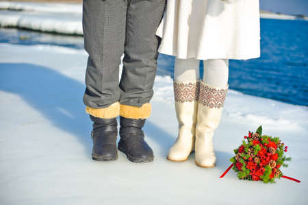 Bouquet of roses and fir cones on the ice and legs of bride and groom Stock Photo