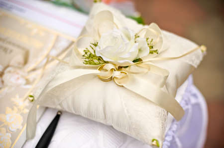 Gold wedding rings on a pillow with a flower ivory