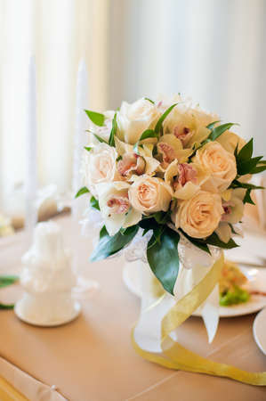 wedding table setting: Ash and tea roses in a wicker basket on an old shabby table.