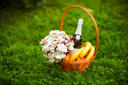 Flowers, champagne and fruit in a basket on the green grass