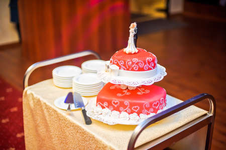 red wedding cake decorated with white patterns