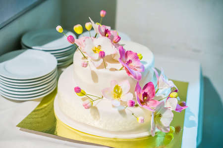 White cake with pink and yellow flowers Stock Photo