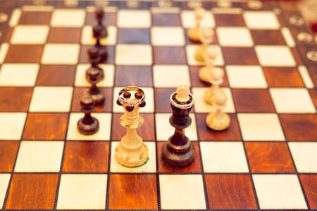 two wedding rings on chessboard. King and queen