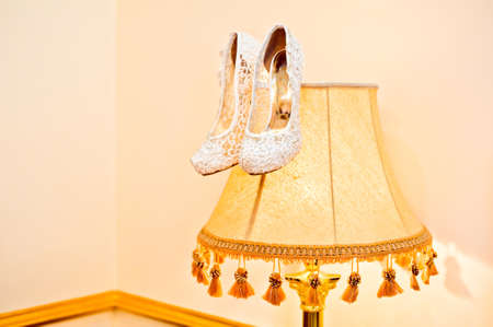 Wedding shoes cream color on a floor lamp