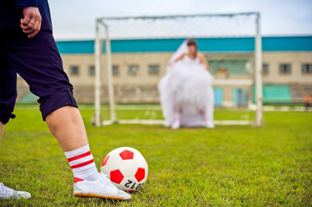 winning pitch: European Football Championship concept. Bride and groom on the football stadium. soccer ball