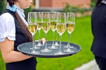 professional waitress in uniform is serving champagne Stock Photo