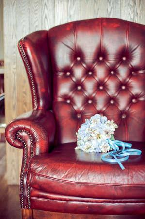 calas blancas: Brides bouquet on a red leather armchair Foto de archivo