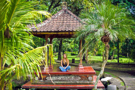 ubud: Young woman relaxing on the porch of house with green garden on the background