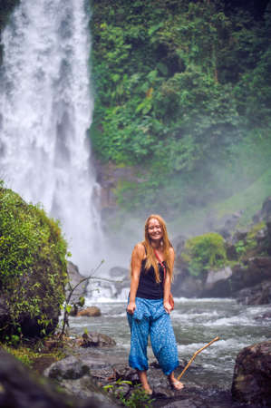 Young woman near waterfall, bali, indonesia travel concept