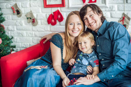 mantelpiece: Family in Christmas decorations on a red couch. Christmas concept