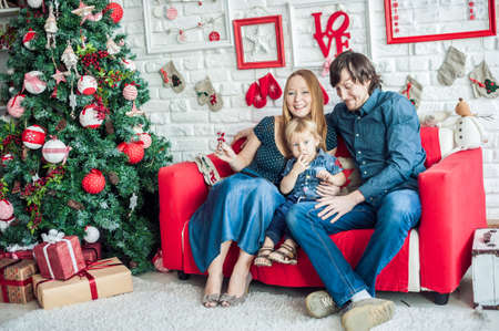 female christmas: Family in Christmas decorations on a red couch. Christmas concept