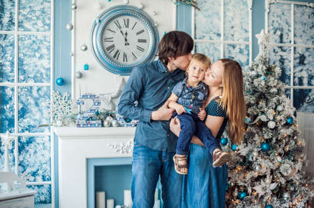 fireplace family: Family standing by the fireplace and Christmas tree. Christmas concept