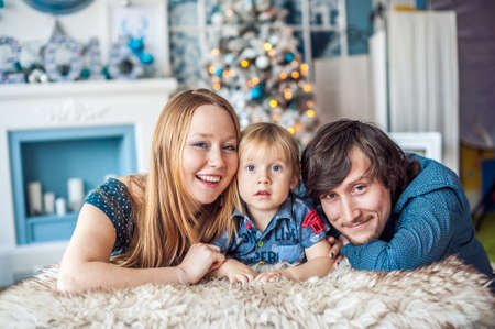 fireplace family: Family sitting by the fireplace and Christmas tree. Christmas concept