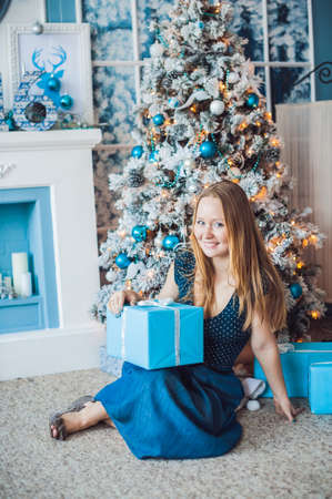new year s eve: The woman at the Christmas tree with New Years gift. Christmas concept