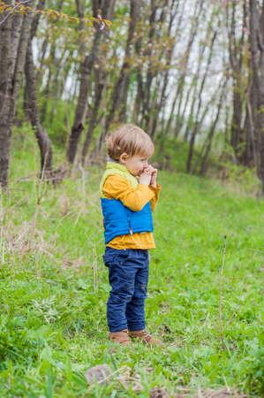 El muchacho del niño corriendo por el jardín en flor