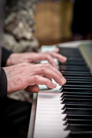 making music: Male hands playing the piano, press the keys, music production concept Stock Photo