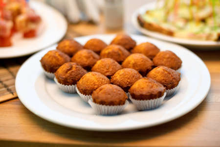 closeup of some appetizing plain muffins in a white ceramic plate on a set table