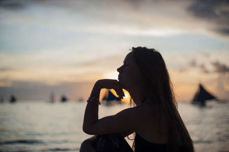 A girl sits on the beach on the island of Boracay in the sunset