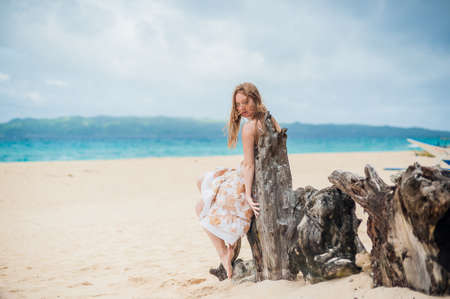 Young girl sitting on an old tree on the beach of Boracay Island Stock Photo