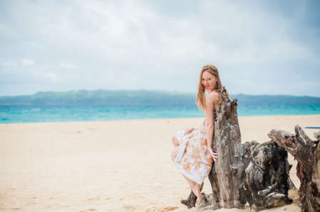 eventide: Young girl sitting on an old tree on the beach of Boracay Island Stock Photo