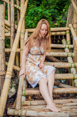 eventide: A girl sits on a bamboo ladder