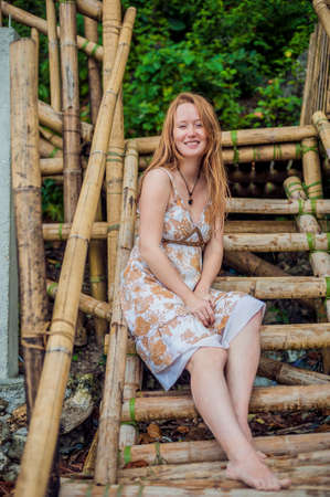 A girl sits on a bamboo ladder