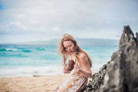A girl sits on a rock on the beach of Boracay Island