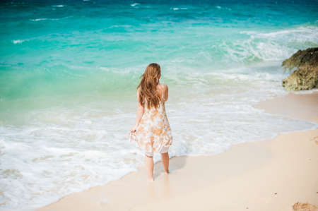 The girl walks on the waters edge on the island of Boracay Stock Photo